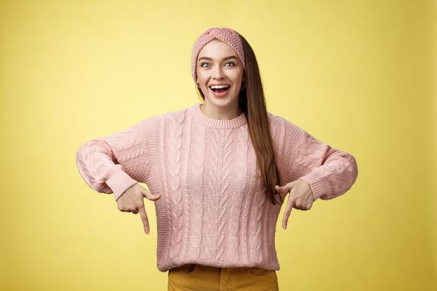 Эйфоричная привлекательная молодая модная девушка в вязаной группе в свитере, восторженно улыбающаяся, восторженно указывая вниз, взволнованная потрясающим продвижением по службе, стоя удивленная и ошеломленная на желтом фоне