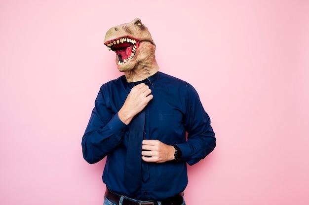 Euphoric man with dinosaur head putting on his tie