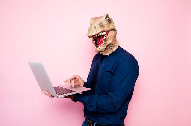 ノートパソコンを使用して恐竜の頭を持つ陶酔男