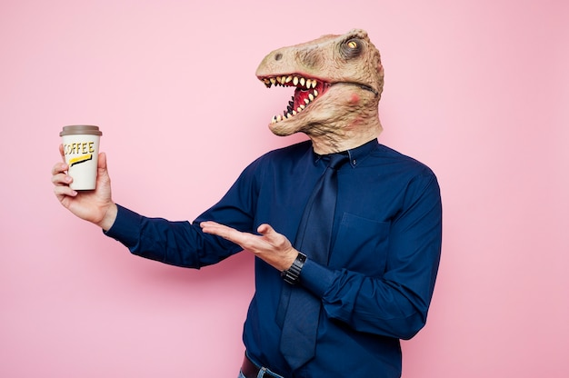 Euphoric man with dinosaur head with coffee to go