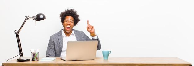 アイデアを実現した後、幸せで興奮した天才のように感じ、元気に指を上げた若い黒人実業家、eureka!机の上