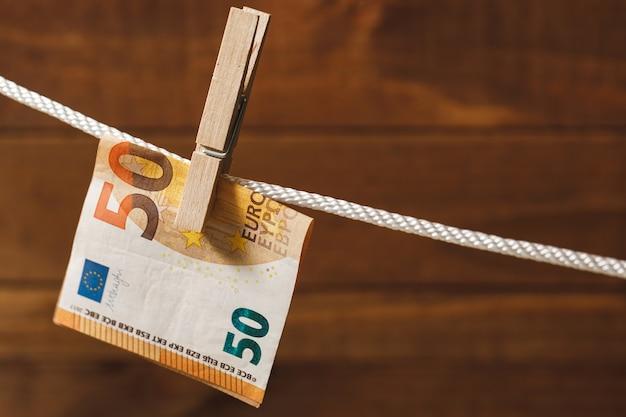 Банкнота евро подвешена на веревку с прищепкой. понятие об отмывании денег.