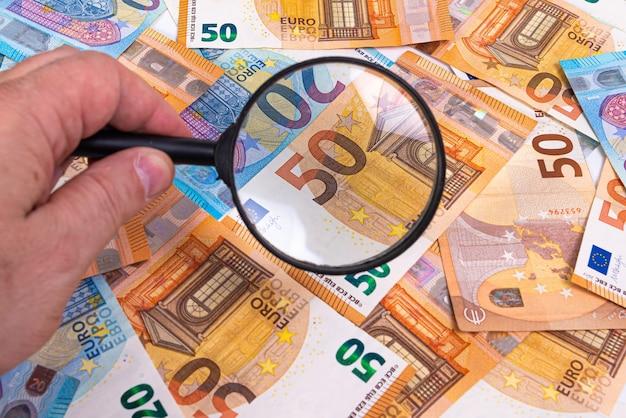 Банкноты евро и увеличительное стекло в руке, крупным планом