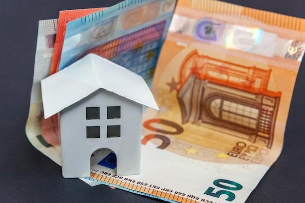 유로 지폐와 상징적 인 작은 장난감 집