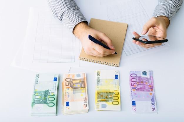 유로 지폐가 쌓여 있습니다. 그의 회계를하는 남자. 소기업의 비용 분배. 저축, 예금, 대출 및 이자율.