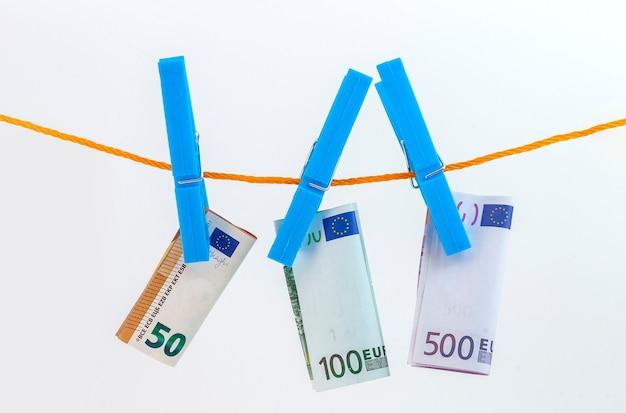 Банкноты евро, прикрепленные прищепками к веревке на белом изолированном фоне
