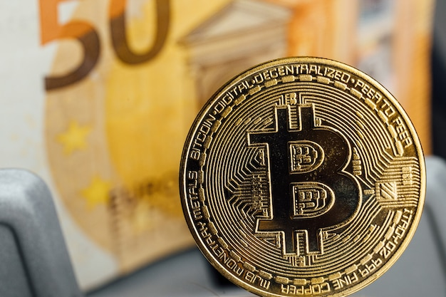 Euro banknotes and bitcoin cryptocurrency investing concept. euro money and crypto currency golden bitcoin coin.