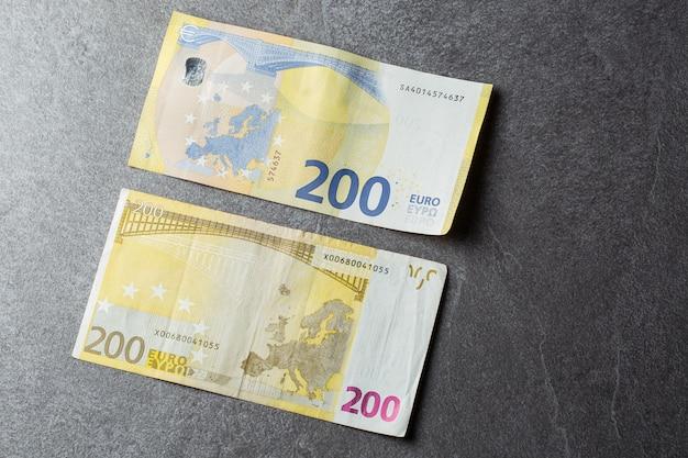 Банкноты евро заделывают. несколько двести евро банкнот на сером фоне 200 евро