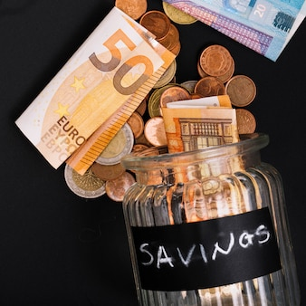 Euro banknotes and coins spilling from open savings glass jar on black background