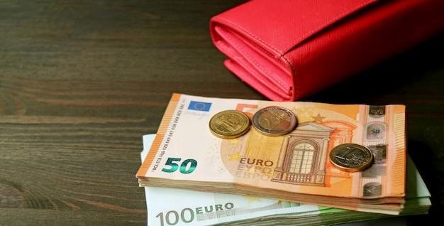 Euro banknotes and coins with various credit cards and a red wallet