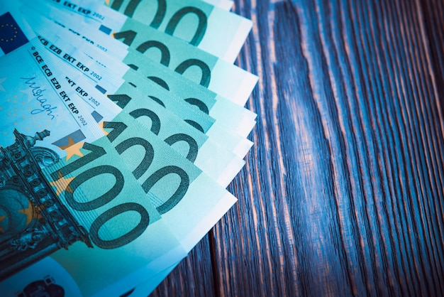 Euro banknotes in fan at wood