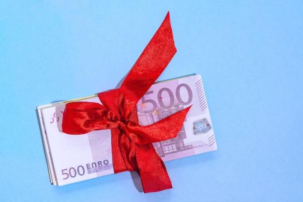 파란색 벽에 붉은 활과 스택에 유로 지폐 5 백. 선물, 보너스 또는 보상 개념.