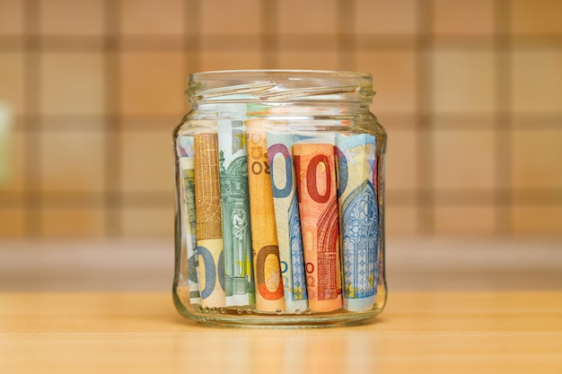 Euro banknotes in a glass jar close-up. the kitchen wall is blurred.