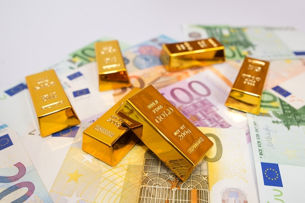 Euro banknotes and gold ingots close up