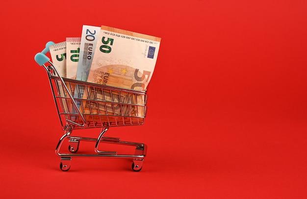 Банкноты евро в корзине на красном