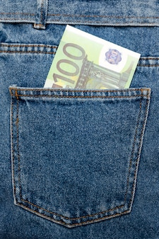Euro banknotes in jeans back pocket.