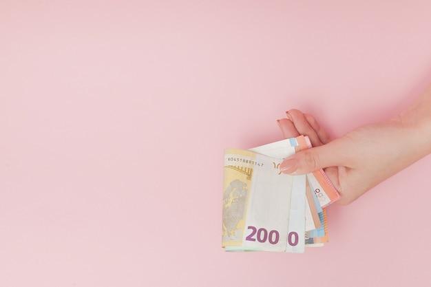 Банкноты евро деньги в женских руках на розовом фоне