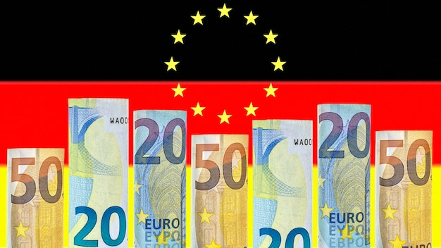 Euro banknotes rolled up in a tube on the background of the flag of germany