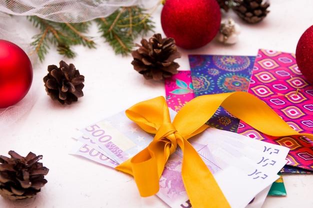 金のリボンで結ばれたユーロ紙幣、お金のための封筒の弓、白い背景、クリスマス、新年