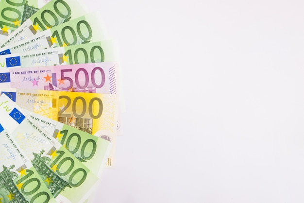 Euro banknotes on a white surface. the money is fanned out. copy space.