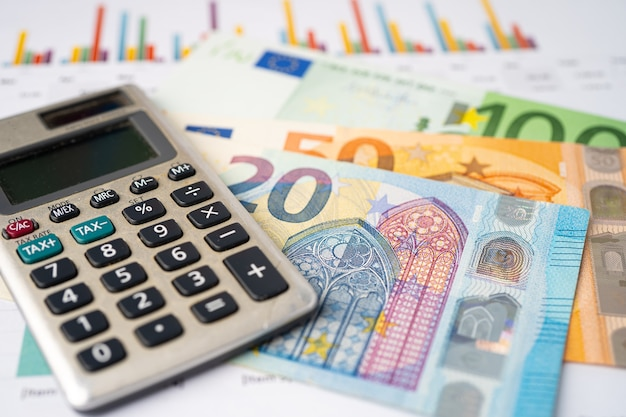 Euro banknotes with calculator on graph background.