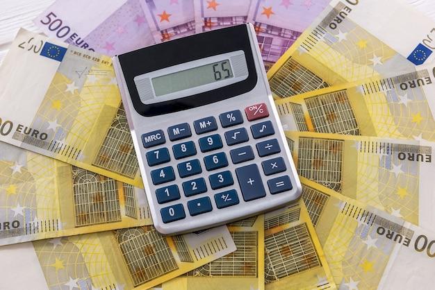 밝은 배경에 계산기와 유로 지폐