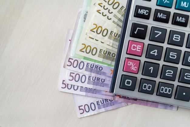 나무 책상에 계산기가 있는 유로 지폐