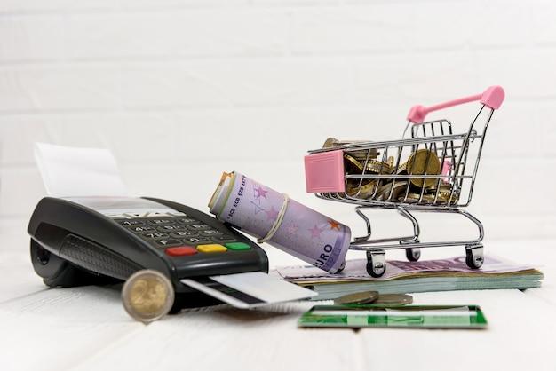 カートに硬貨が入ったユーロ紙幣とカードが付いた銀行ターミナル