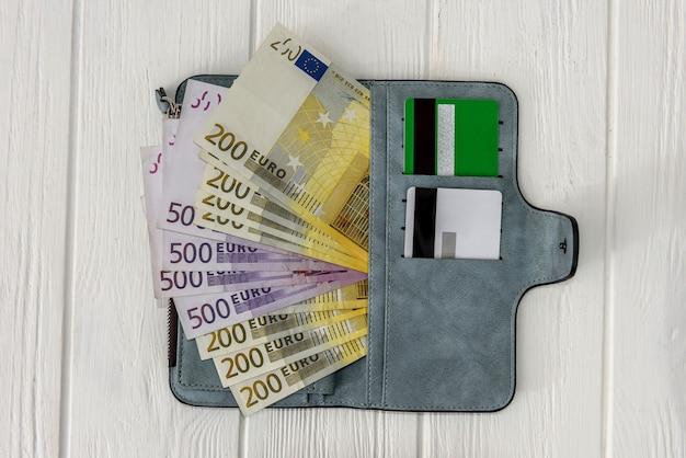 Банкноты евро с кредитной картой в кошельке