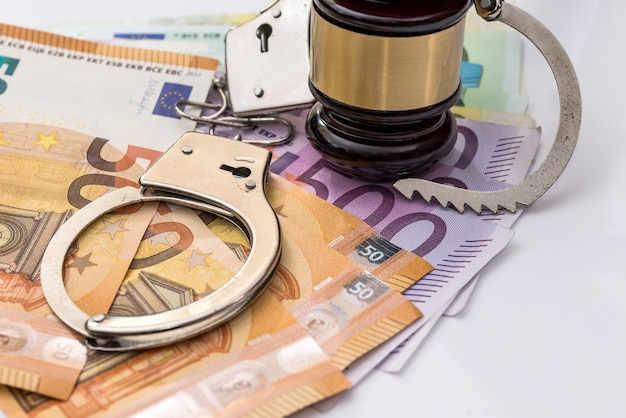 Euro banknotes with handcuffs and gavel on white background