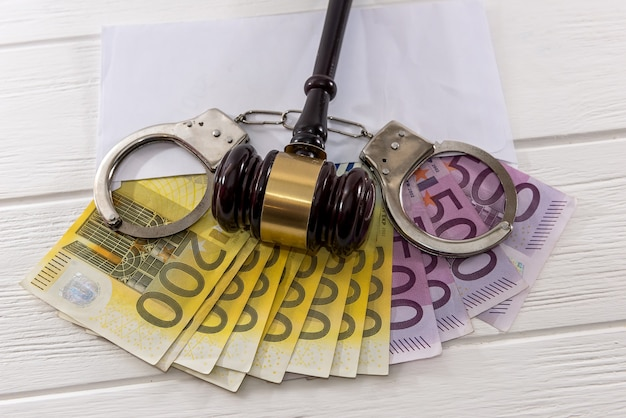 Euro banknotes with judge's gavel and handcuffs