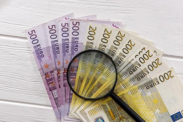 Банкноты евро с увеличительным стеклом на столе