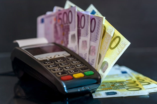 Euro banknotes with terminal on black surface