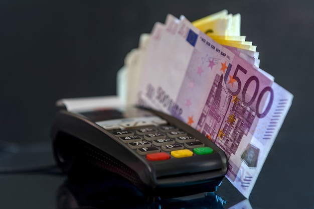 Euro banknotes with terminal on black table