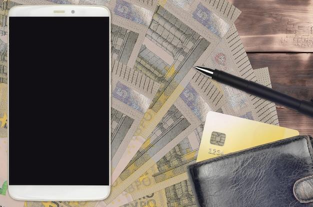 ユーロ紙幣と財布とクレジットカード付きのスマートフォン