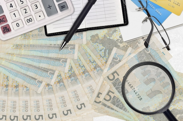 Euro bills and calculator with glasses and pen