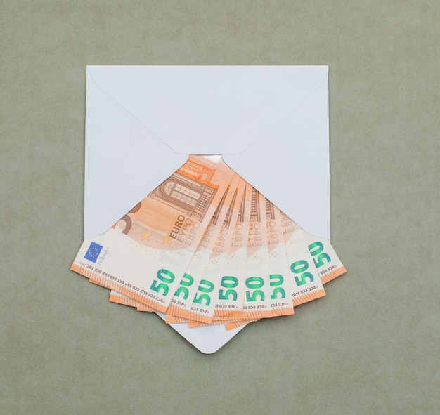 Euro bills in envelope on greenish grey table .
