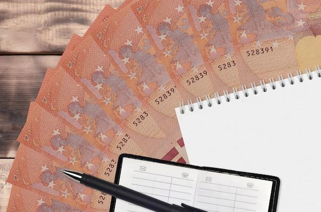 ユーロ紙幣のファンと連絡帳と黒のペンでメモ帳