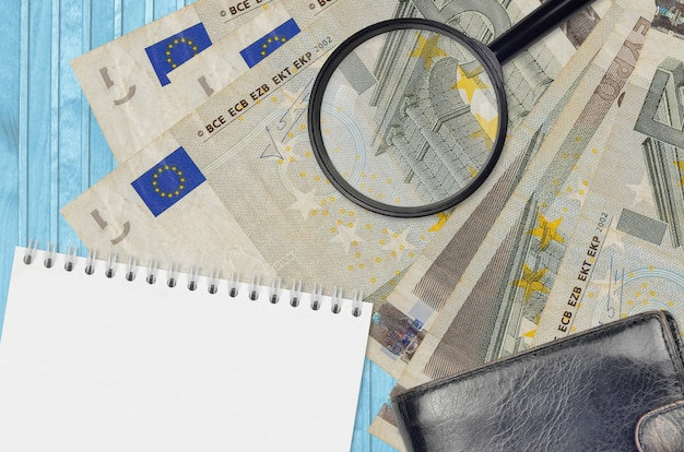 Euro bills and magnifying glass with black purse and notepad