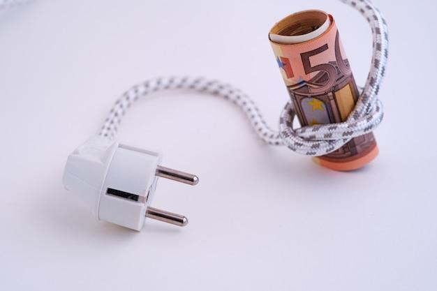 ユーロ紙幣は、アイロンからのワイヤーに結び付けられています。エネルギーコストの上昇に関する概念イメージ