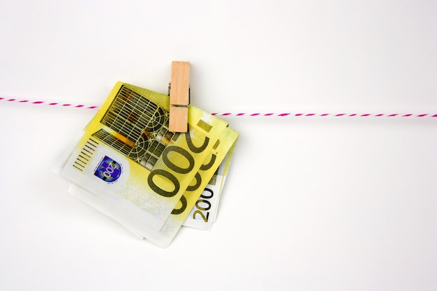 Euro bills with clothespins hang on a rope