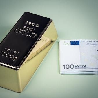 Евро наличными и золотой слиток на зеленом фоне
