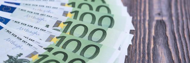 Банкноты наличных евро на темном деревянном пространстве.