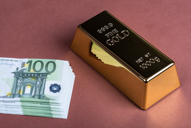 Euro cash and gold bar on a brown surface.