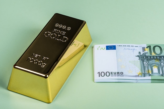 Euro cash and gold bar on a green background