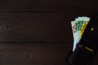 Euro cash in brown wallet on wooden background