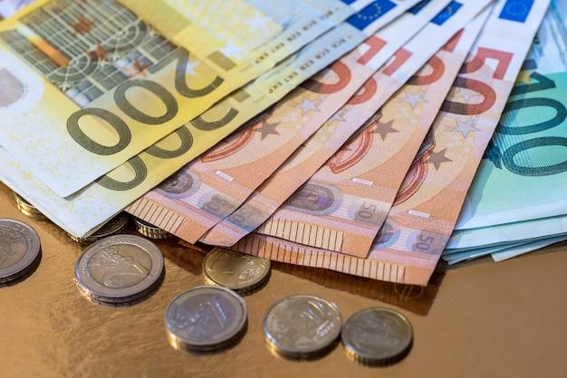 유로 동전과 금에 고립 된 지폐