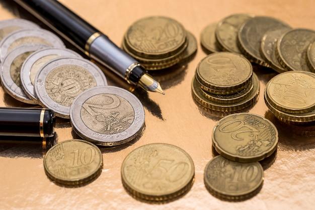 ユーロ硬貨と金で隔離のペン