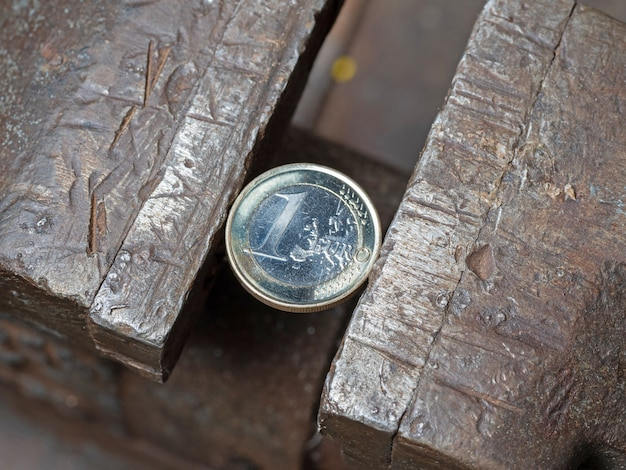A euro coin held in a metal grip