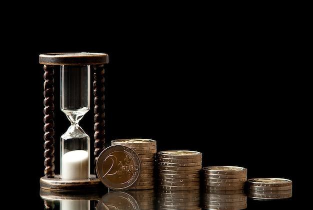 Монеты евро и песочные часы на черном фоне. студийный снимок.